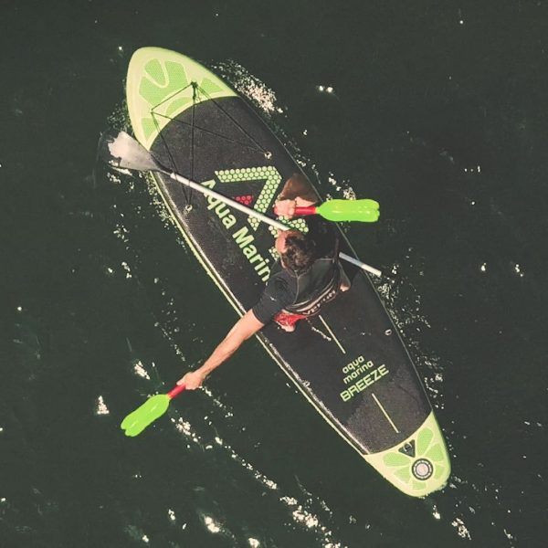 Workout with Indian clubs on yoga and SUP stand up paddle board